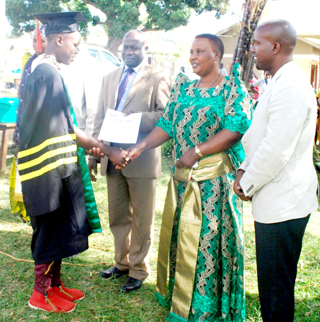 A graduand recieves his certificate from Kyotera Woman MP Robinnah Ssentongo as Mr Rugambwa,the Kitovu Mobile CEO looks on.