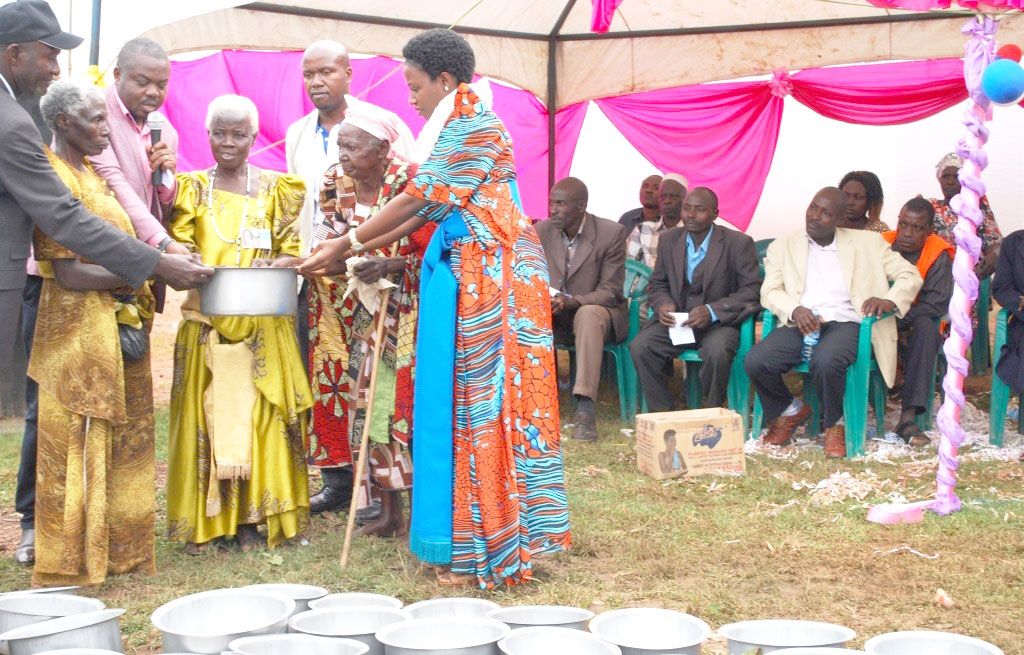 Area MPs Mr Amos Mandela (2rd left) and Ssubi Kinyamattama (right) giving grand mothers saucepans.