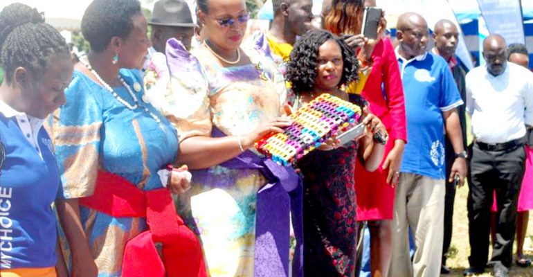 Chief Guest Ms Watuwa,the outgoing RDC Kyotera overwhlemed by a hand bag made by the craft graduands.
