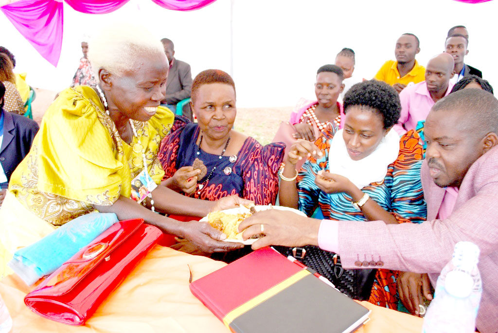 MPs (Ssuubi Kinyamatama and Amos Mandela get their share of the cake during the function