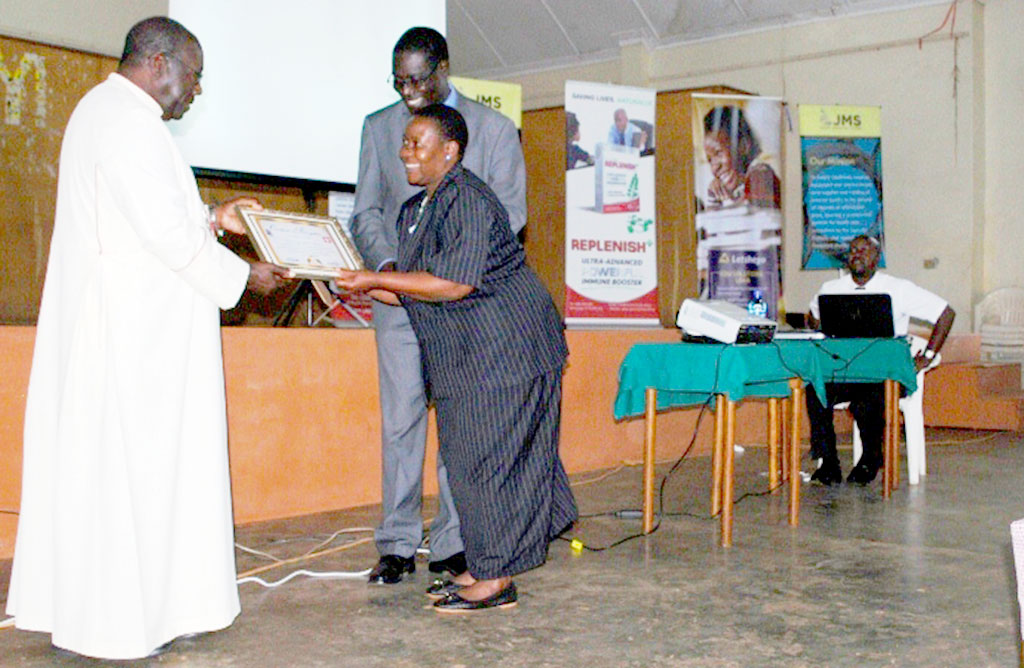 Ms Katerega receives a certificate from Masaka Diocesan Bishop John Baptist Kaggwa in recognition of her dedicated years of service .