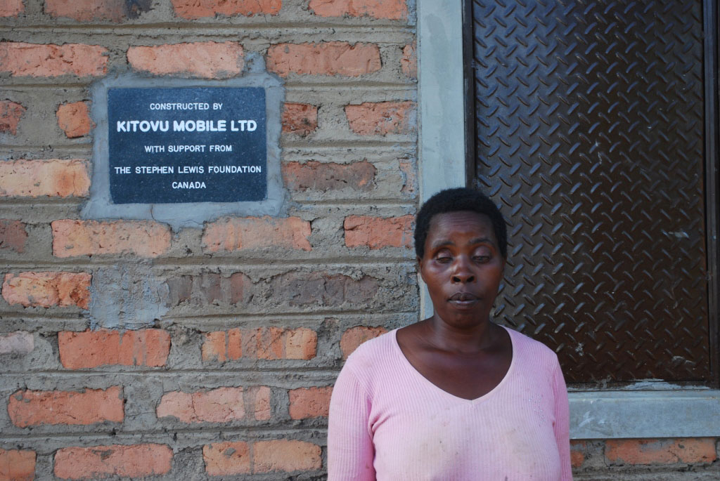Aisha Namulema stands infront of her new house constructed by Kitovu Mobile