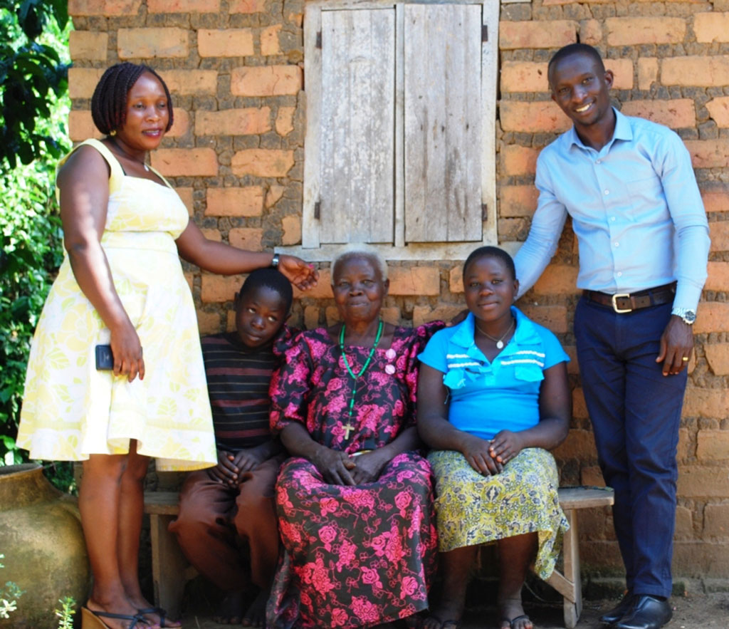 Grandmothers and OVC project cordinators,Emma and Sharon,pose for a photo with Namatovu's family.