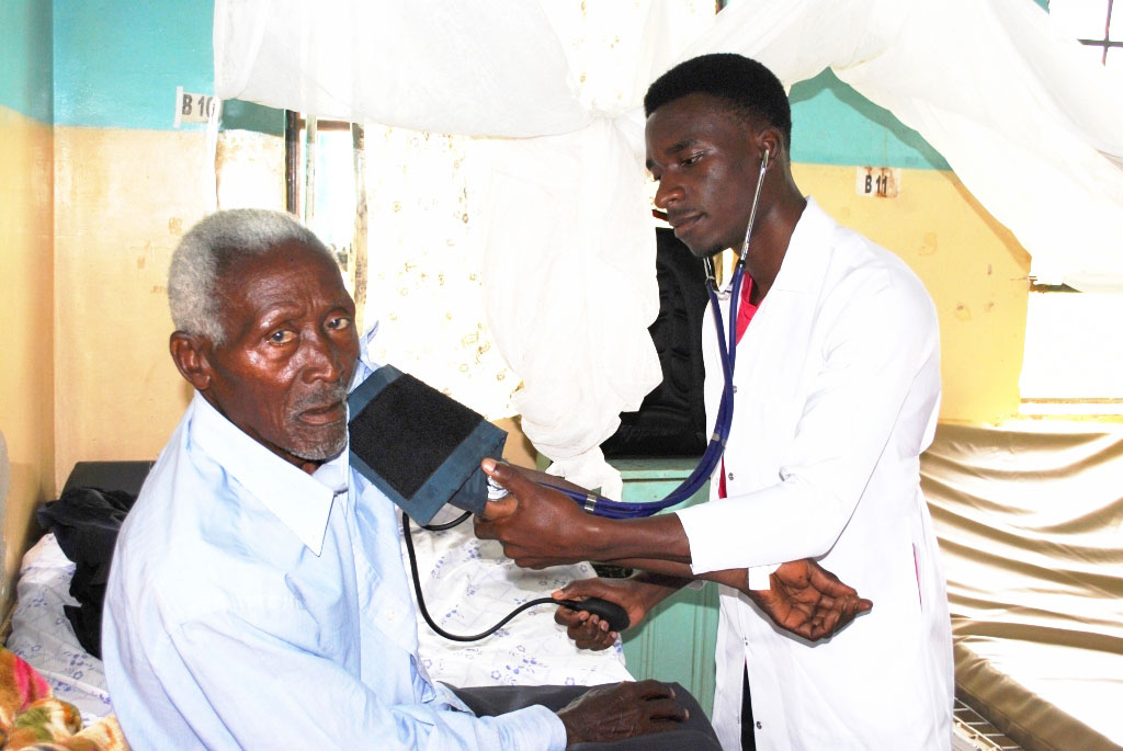 Matovu monitors a patient's blood pressure at the hospital male ward.