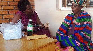 Ms Rose Nabatanzi,the in charge Kitovu Mobile Medical Center,consells a visibly worried cervical cancer patient before giving her liquid oral morphin,to relieve her of pain. KITOVU MOBILE PHOTO.