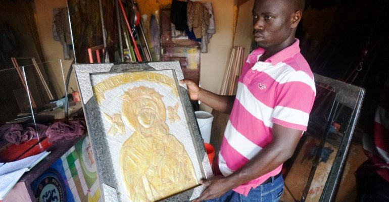 Ssekitoleko with a potrait of Divine Mary. He does such pieces,earning good money from them.