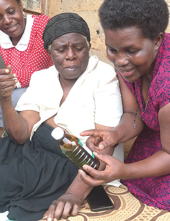 ose-Nabatanzi-the-in-charge-at-Kitovu-Mobile-Medical-Centre-showing-the-morphine-bottle-to-Janet-Nabadda.jp