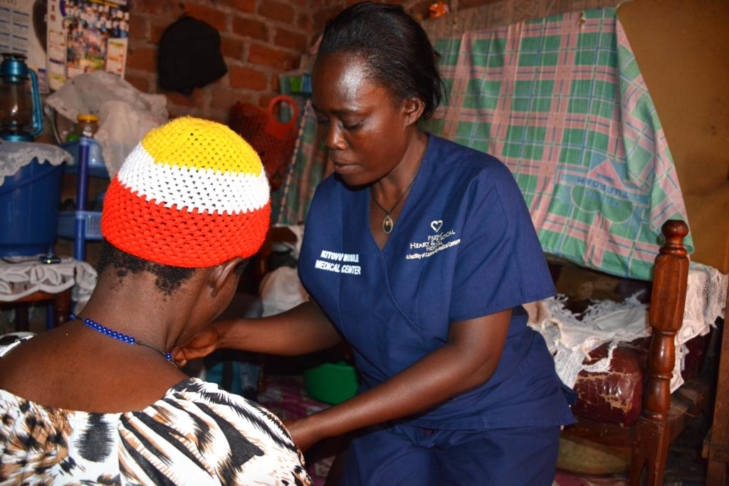 Ms Nasuna in blue medical uniform checks on Nabosa's one-month baby during a home visit.