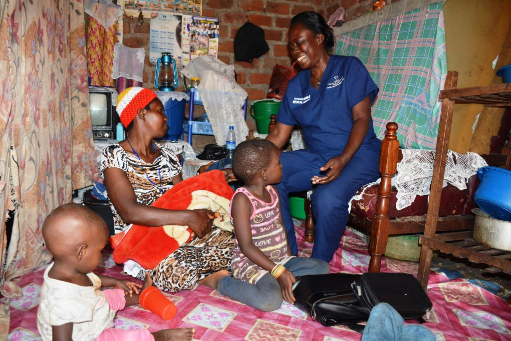 Nabossa putting on a holding her baby poses for a photo with her other children.