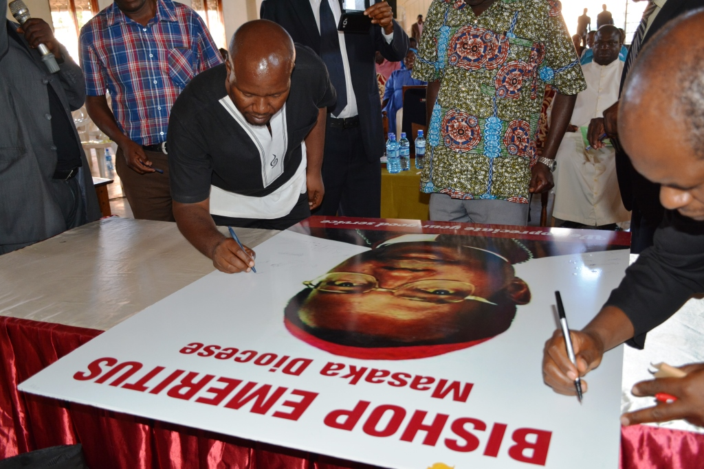 Mr Rugambwa,Kitovu Mobile CEO,signs on Bishop Kaggwa's photo in recognition of his selfless service to the Diocesan Health issues
